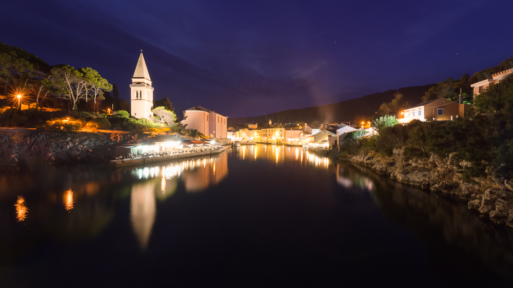 Nachthimmel über dem beleuchteten Hafen und der Altstadt des Küstenstädtchen Veli Lošinj mit der Kirche S. Antonio Abate, Lošinj, Kvarner Bucht, Kroatien