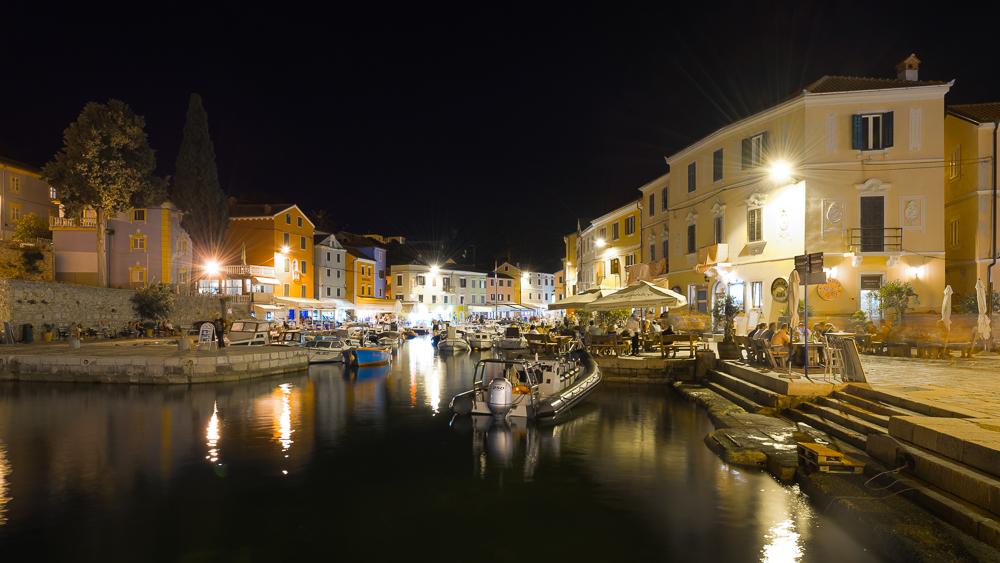 Menschen sitzen in Restaurants im beleuchteten Hafen in der Altstadt des Küstenorts Veli Lošinj bei Nacht, Lošinj, Kvarner Bucht, Kroatien