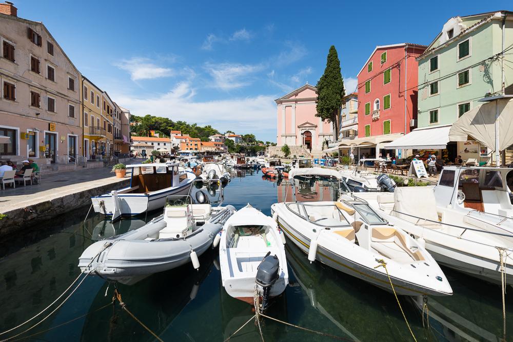 Boote und bunte Hausfassaden im Sonnenlicht im Hafen in der Altstadt von Veli Lošinj auf der Insel Lošinj, Kvarner Bucht, Kroatien