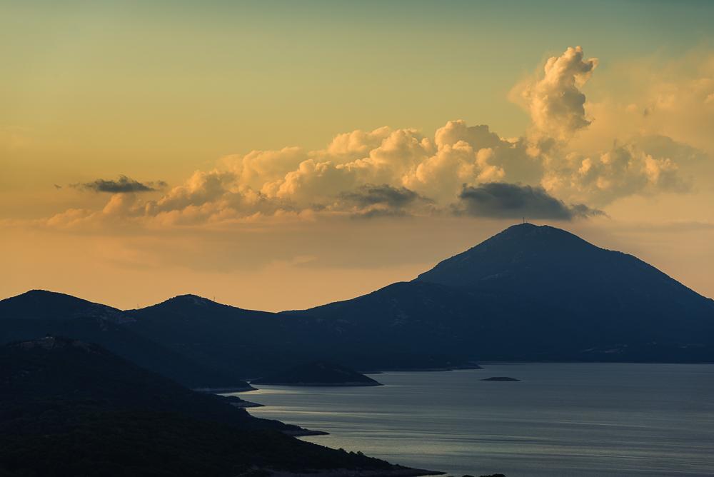 Der Berg Osoršćica und die Küste der Insel Lošinj vor Cumuluswolken im leuchtenden Abendlicht vor Sonnenuntergang, Lošinj, Kvarner Bucht, Kroatien