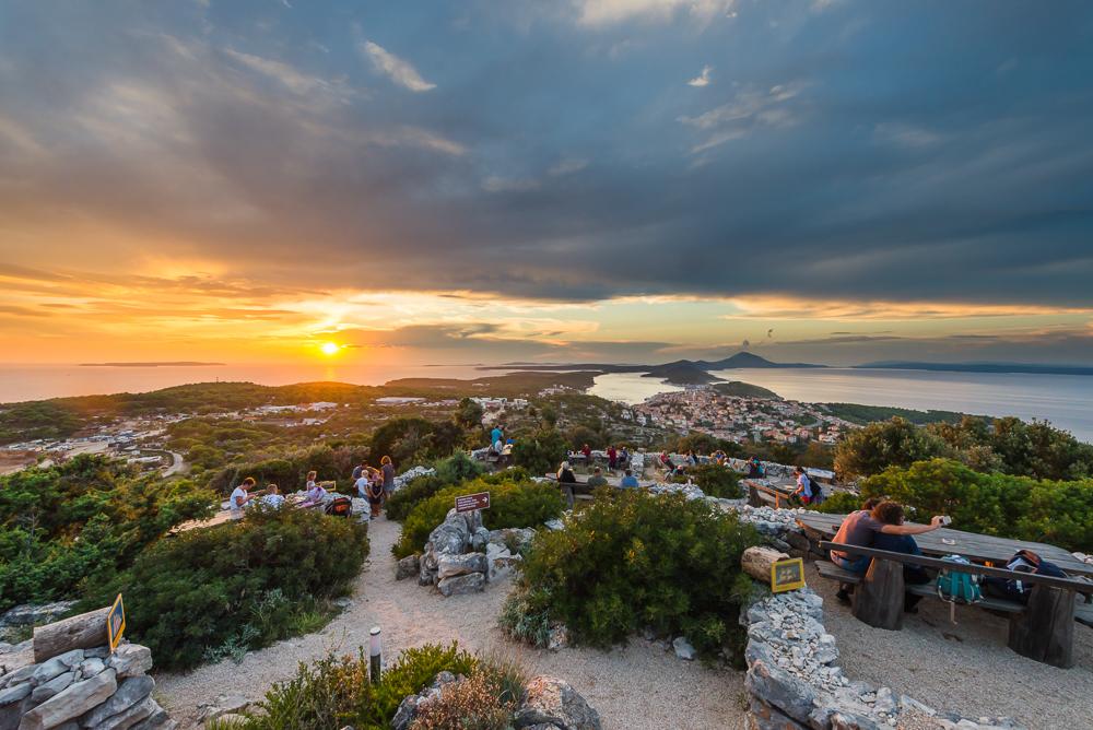 Menschen sitzen an den Bänken der Bar Providenca und geniessen die Aussicht auf den Sonnenuntergang über der Insel Lošinj und Cres, Kvarner Bucht, Kroatien