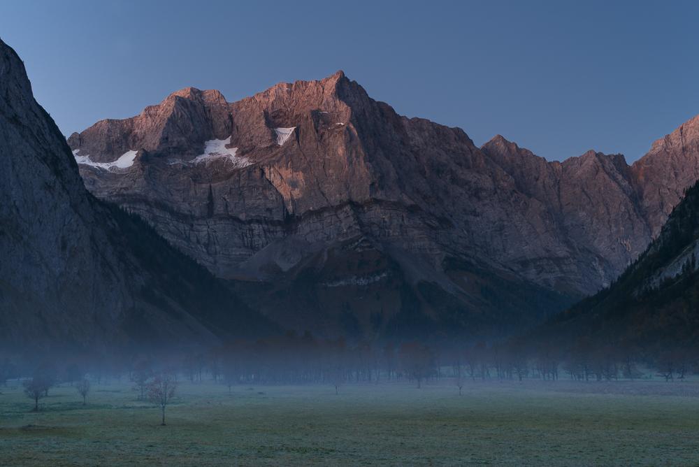 Nebelschwaden auf dem herbstlichen Ahornboden vor den Felswänden des Karwendelgebirges in der rötlichen Morgendämmerung, Tirol, Österreich