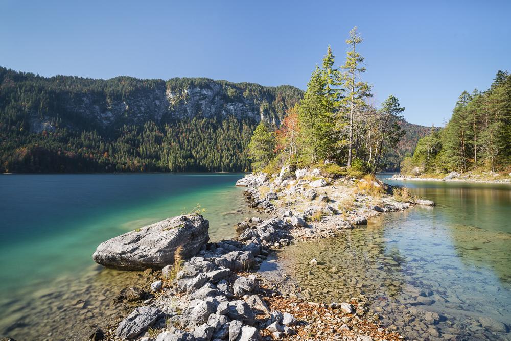 Steine am Ufer der Braxeninsel im Eibsee umgeben von Herbstwald, Bayern, Deutschland