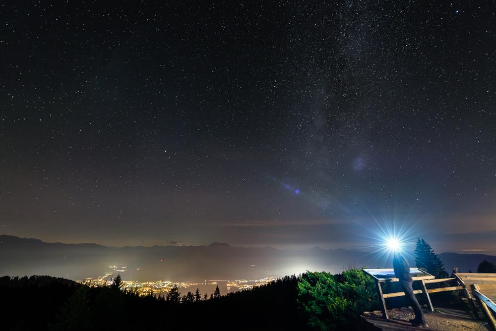 Blick von der Neureuth-Hütte auf den Sternenhimmel über dem nächtlich beleuchteten Rottach-Egern am Tegernsee, Bayern, Deutschland