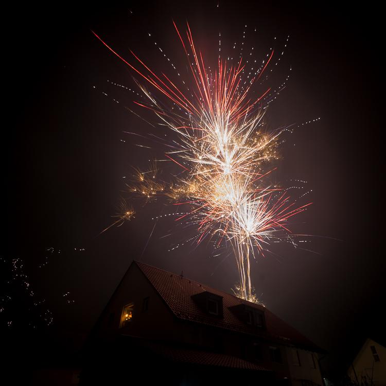 Mann mit Wunderkerze im Fenster eines Wohnhauses und Feuerwerk an Neujahr 2019