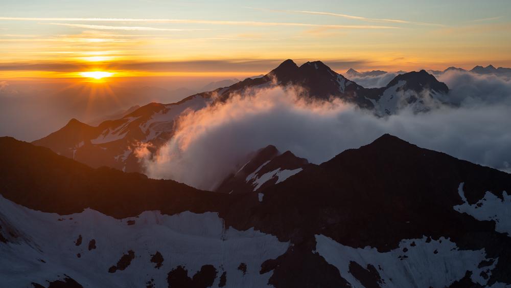 Sonnenaufgang über wolkenverhangenen Berggipfeln von Feuerstein und Agglsspitze am Becherhaus, Stubaier Alpen, Südtirol