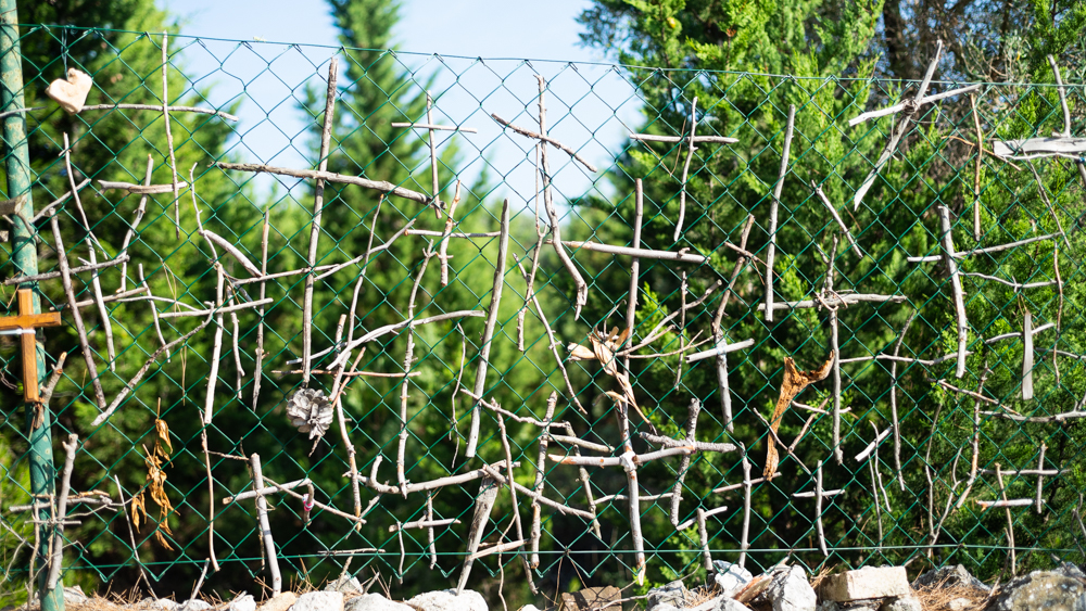 Holzkreuze am Zaun der Kirche Sv. Salvadur oberhalb der Stadt Cres auf der Insel Cres, Kvarner Bucht, Kroatien