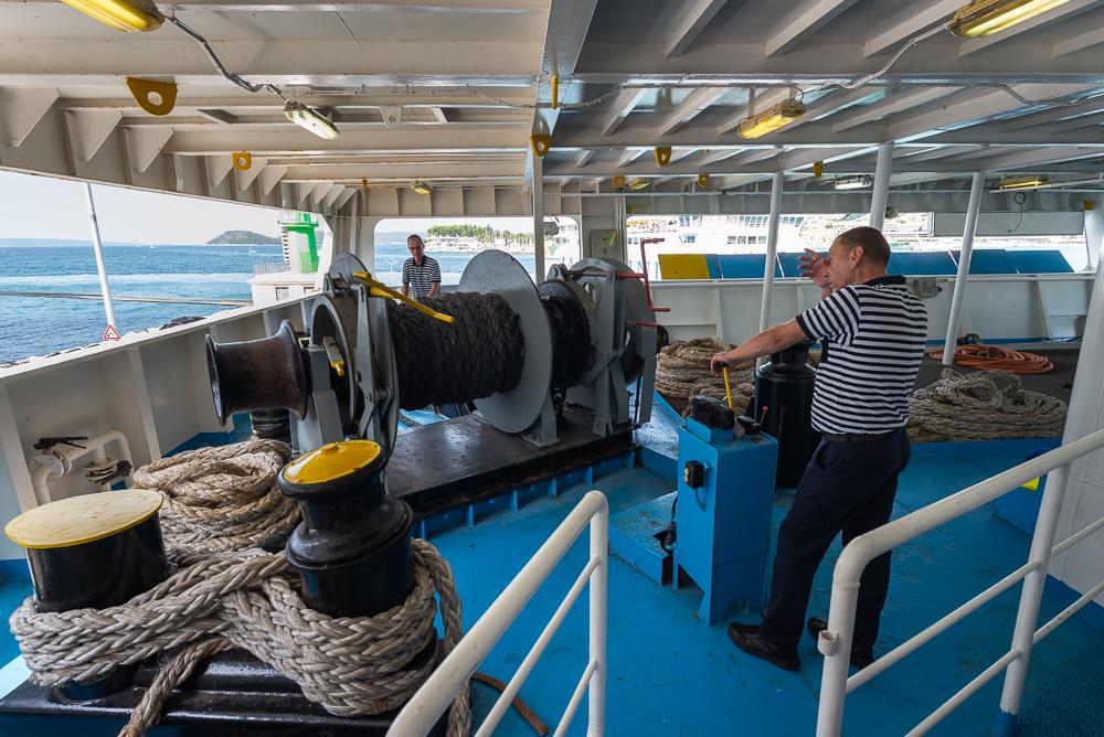 Zwei Männer arbeiten und schwitzen an der Seilwinde für die Haltetaue beim Ablegen der Fähre im Hafen von Split, Dalmatien, Kroatien