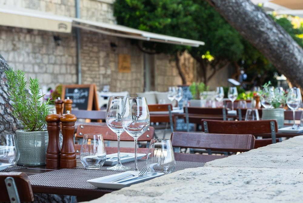 Eingedeckte Tische mit Besteck und Weingläsern auf der Terasse eines Restaurants auf der Stadtmauer der Altstadt von Korčula, Süddalmatien, Kroatien