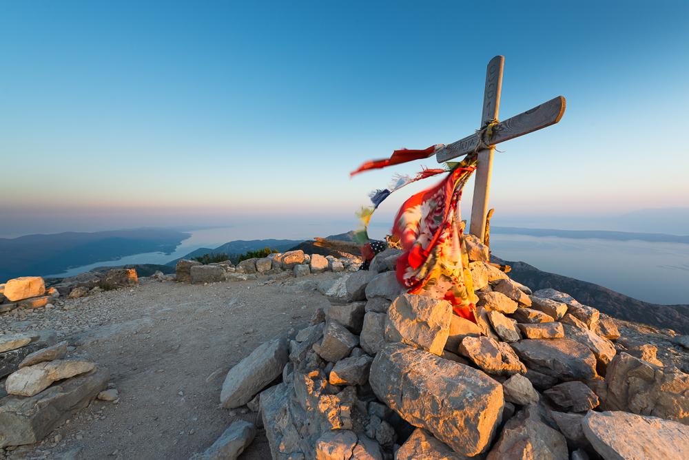 Das Gipfelkreuz auf dem Gipfel des Berges Sv. Ilija auf der Halbinsel Pelješac vor einem Inselpanorama, Süddalmatien, Kroatien