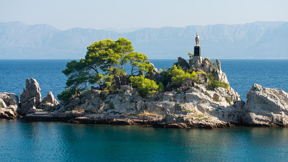 Eine weisse Madonnen-Statue steht auf einem Felsen im Hafen von Trpanj vor der Kulisse der Berge der Makarska Riviera, Pelješac, Dalmatien, Kroatien
