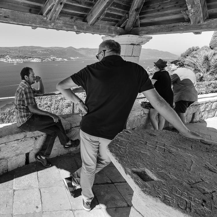 Unterhaltung zwischen Männern im Schatten der Loggia vor dem Franziskanerkloster bei Orebic mit Blick auf Korcula, Halbinsel Peljesac, Dalmatien, Kroatien