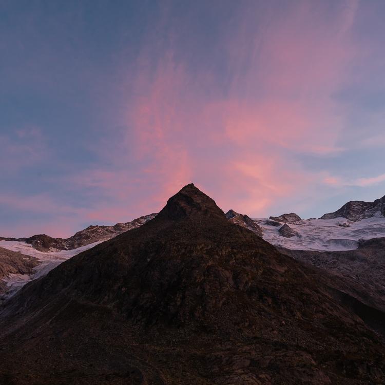 Das pyramidenförmige Steinmandl vor Geltschern, Berggipflen und den rötlichen Schleierwolken bei Sonnenuntergang an der Berliner Hütte, Zillertal, Tirol, Österreich