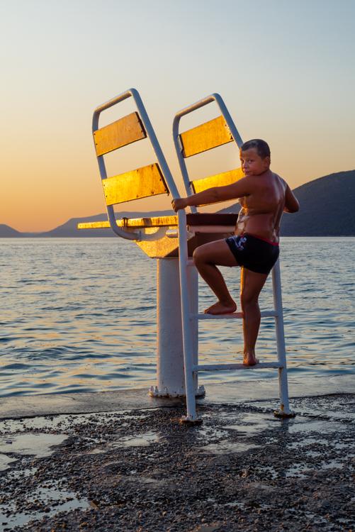 Junge springt vom Sprungbrett auf einem Sprungturm ins Mittelmeer auf der Insel Cres in der Kvarner Bucht bei Sonnenuntergang, Kroatien
