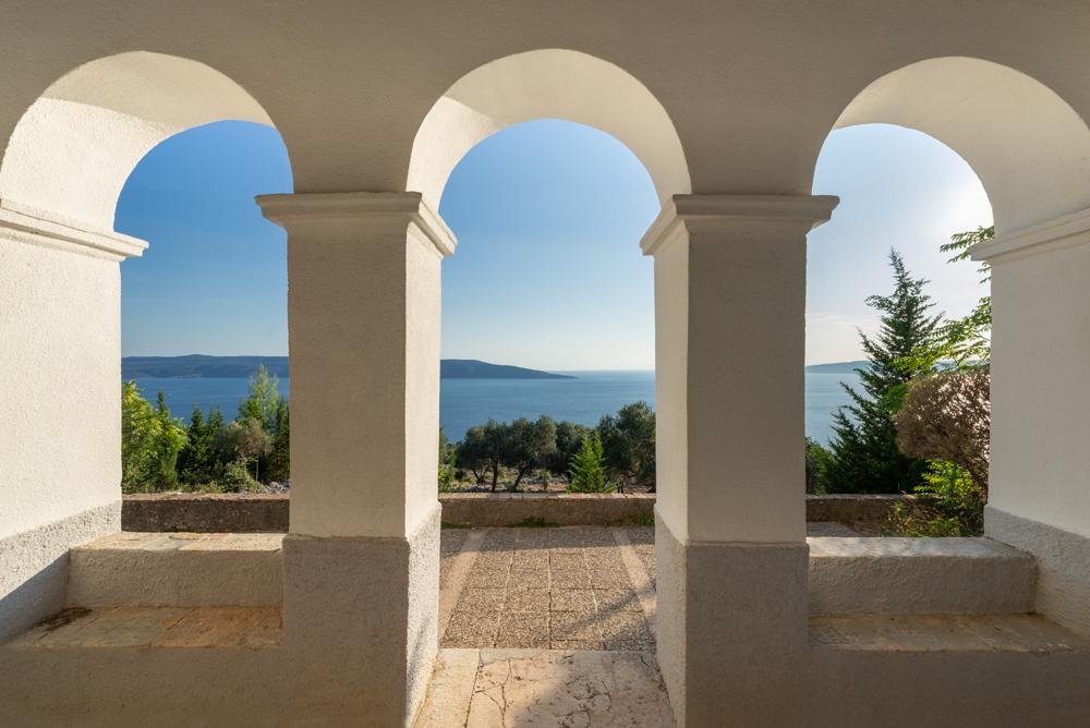 Blick durch die Rundbögen der Fassade der Kapelle Sv. Salvadur auf Cres auf das Meer bei Sonnenschein, Kvarner Bucht, Kroatien