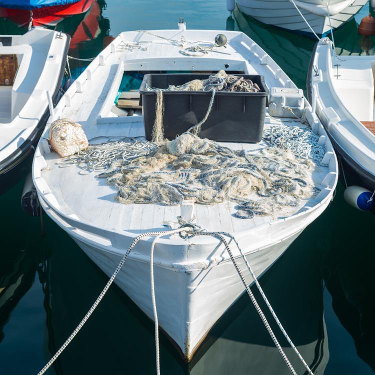 Weisses Fischerboot mit Tau und Fischernetz auf Deck leuchtet hell in der Morgensonne im Hafen von Cres, Kvarner Bucht, Kroatien
