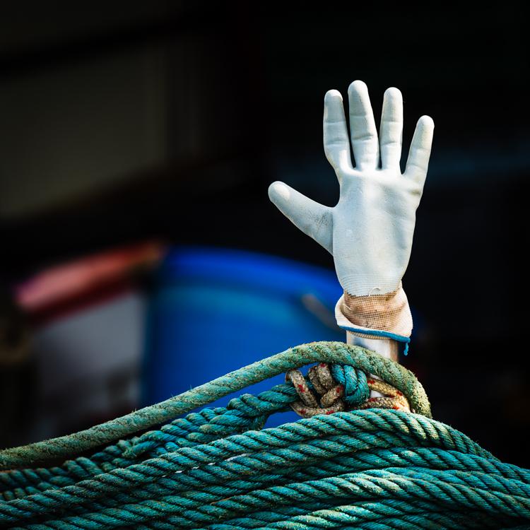Weisser Gummihandschuh steckt auf einem Stab oberhalb eines türkisen Tau auf einem Fischerboot im Hafen von Cres, Kroatien