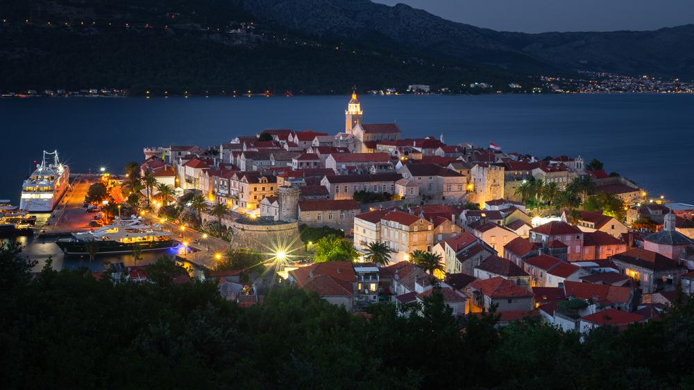 Blick auf die mittelalterlichen Gassen und Gebäude der historische Altstadt von Korcula vor der Insel Peljesac nach Sonnenuntergang, Süddalmatien, Kroatien