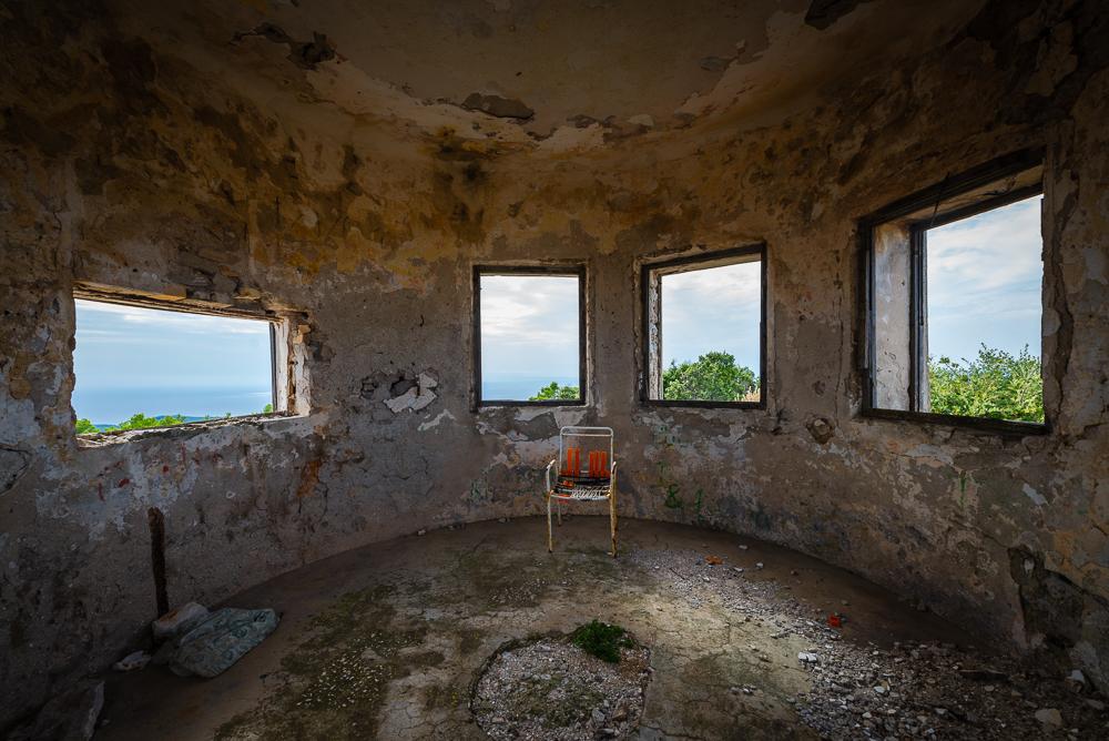 Kaputter Stuhl vor Fenstern in der Ruine einer Festung aus dem 19. Jahrhundert auf dem Berg Hum nach der Stadt Velu Luka auf der Insel Korčula, Kroatien