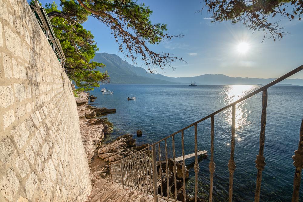 Treppe hinunter zu Felsen am Wasser unterhalb der Stadtmauer von Korcula mit Blick auf Kanal und Berge von Peljesac, Dalmatien, Kroatien
