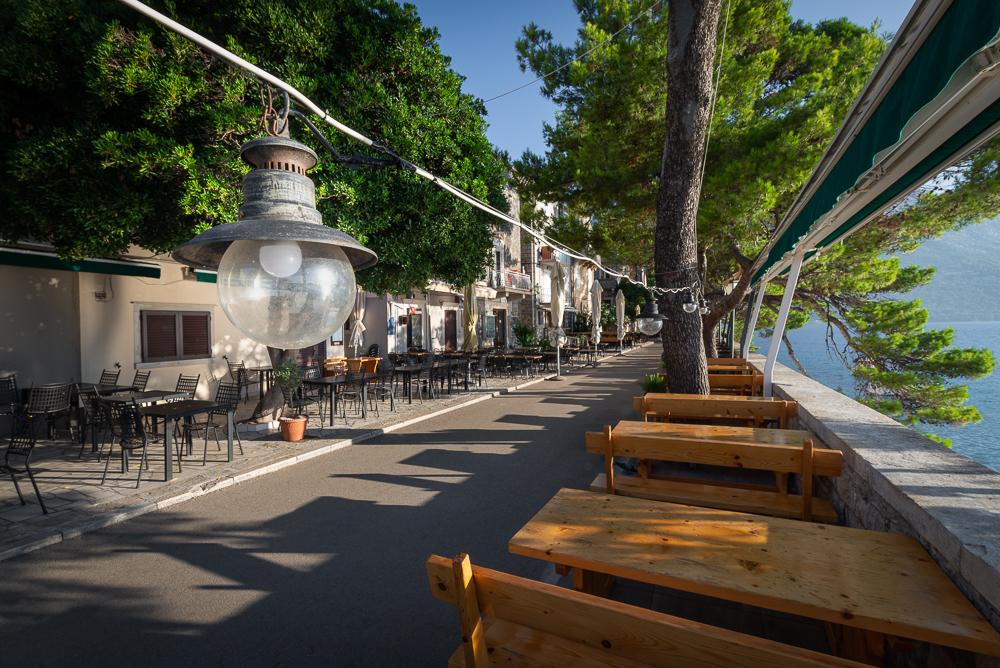 Leere Tische und Stühle auf den Terassen der Restaurants an der Satdtmauer der Altstadt von Korčula in der Morgensonne, Insel Korčula, Süddalmatien, Kroatien