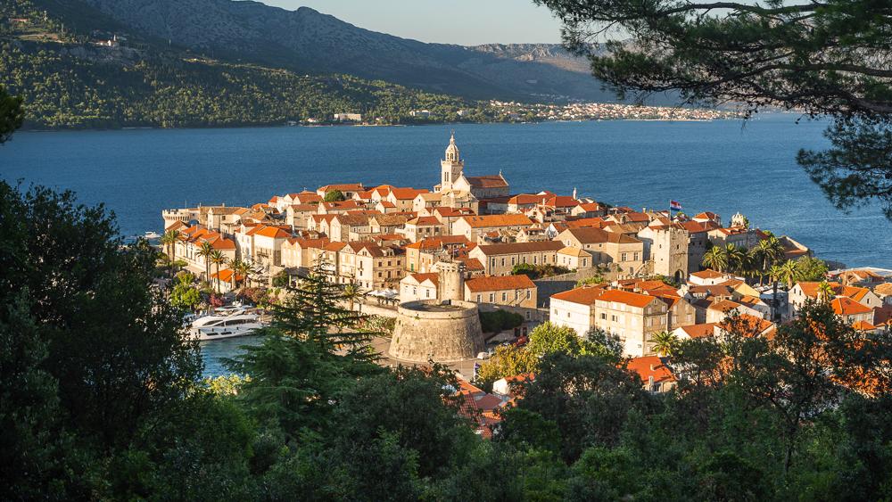 Blick auf die mittelalterlichen Gassen und Gebäude der historische Altstadt von Korcula vor der Insel Peljesac bei Sonnenuntergang, Süddalmatien, Kroatien