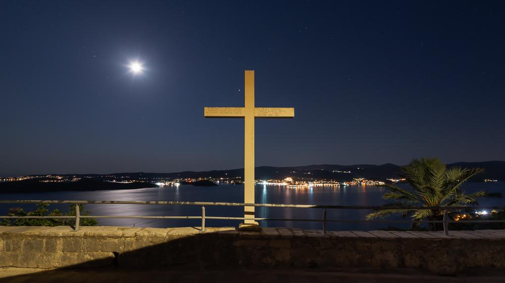 Steinernes Kreuz im Mondschein am Franziskanerkloster bei Orebic auf der Halbinsel Peljesac vor der nächtlich Beleuchteten Altstadt von Korcula, Dalmatien, Kroatien