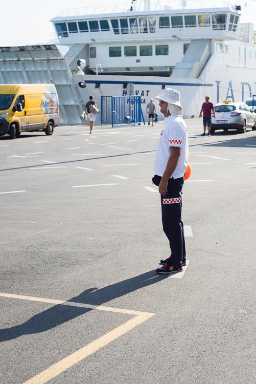 Männlicher Einweiser für die Fahrzeuge beim Boarding einer Fähre steht in der Morgensonne am Fähranleger im Hafen von Split, Kroatien