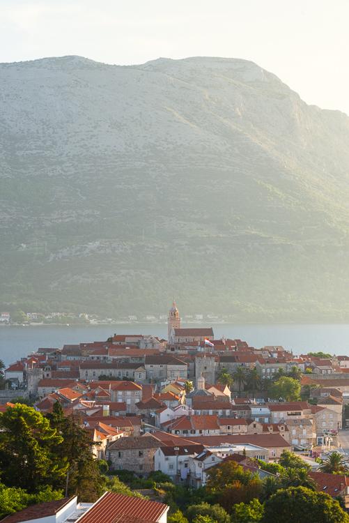 Die Altstadt von Korčula vor dem Gebirgsmasssiv des Sv. Ilija auf der Halbinsel Pelješac im Gegenlicht der Morgensonne, Insel Korčula, Süddalmatien, Kroatien