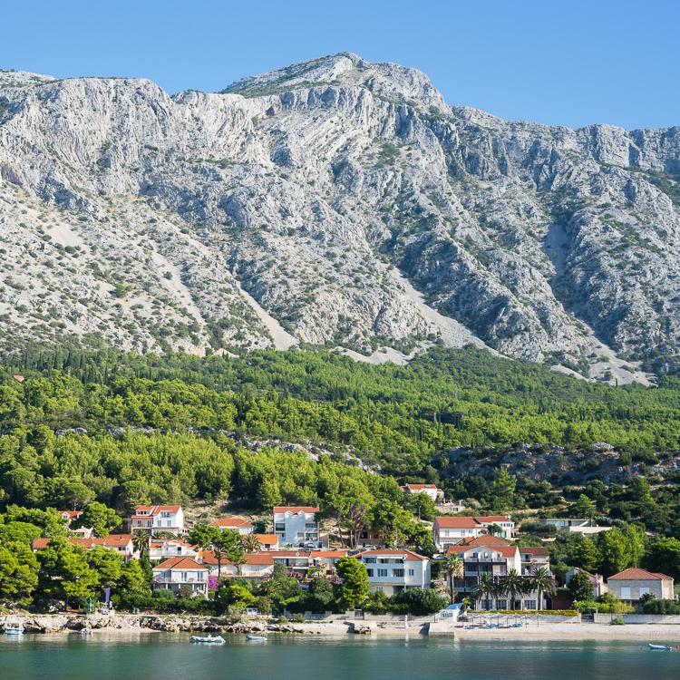 Häuser der Stadt Orebic am Sandstrand vor den grünen Hängen und karstigen Felswänden des Sveti Ilija Bergmassivs auf der Halbinsel Peljesac, Dalmatien, Kroatien