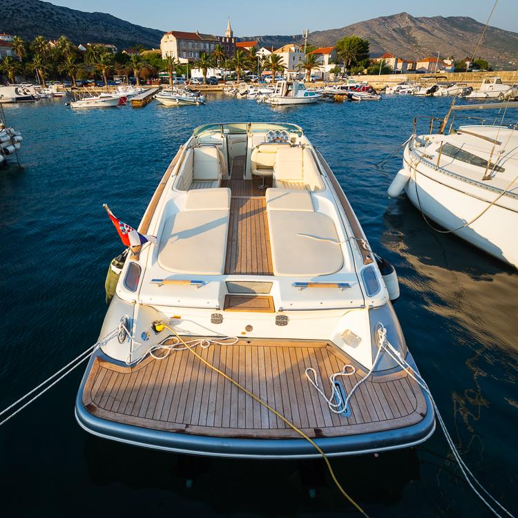Motorboote und Segelboote im Hafen der Stadt Orebic vor den grünen Hängen und karstigen Felswänden des Sveti Ilija Bergmassivs auf der Halbinsel Peljesac in der Abvendsonne, Dalmatien, Kroatien