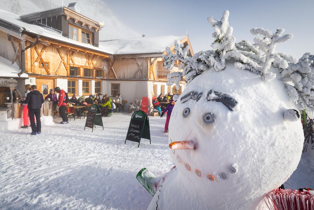 Schneemann auf der Sonnenterasse der verschneiten Hochfeldernalm-Hütte im Skigebiet Ehrwalder Alm, Österreich, Tirol