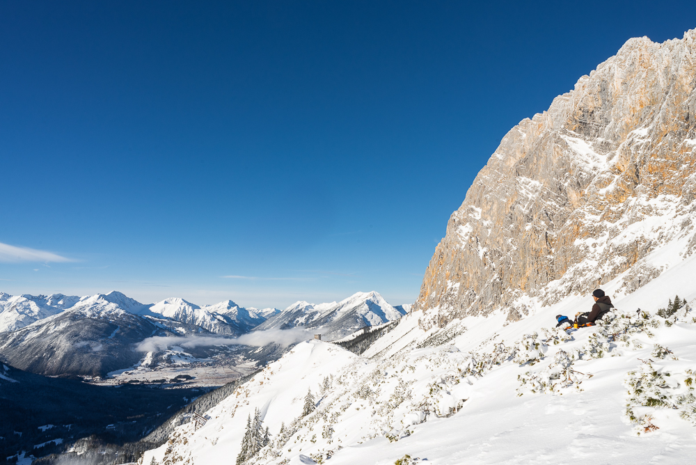 Skitourengeher rasten auf dem Issentalkopf vor einem winterlichen Panorama von Ehrwalder Becken, Ehrwalder Sonnenspitze, Zugspitzmassiv, Ammergauer und Lechtaler Alpen