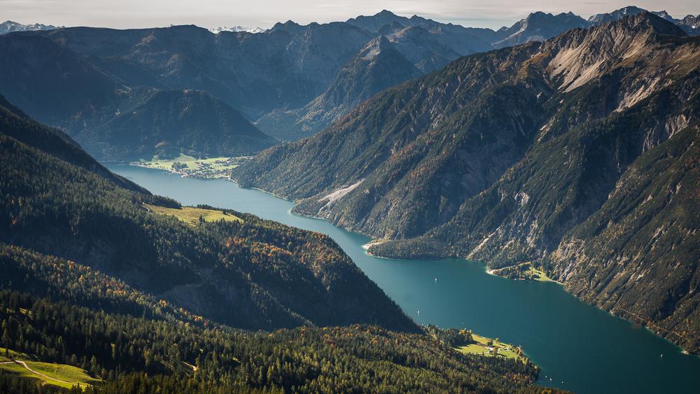 Blick vom Vorderunnütz auf die Gebirgslandschaft mit herbstlichen Bergwäldern und dem türkisfarbenen fjordartigen Achensee, Tirol,Österreich
