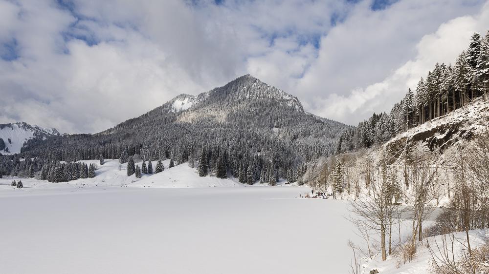 Blick vom Parkplatz an der Taubensteinbahn über dem zugefrorenen Spitzingsee und der Brecherspitze in den bayrischen Alpen