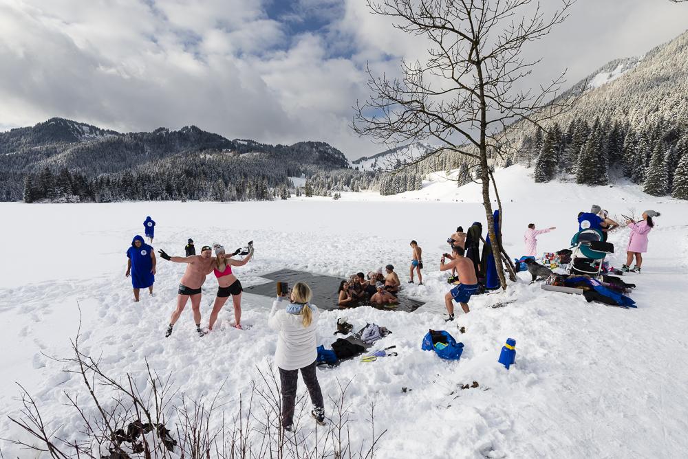 """Ein polnische Gruppe von Männern und Frauen genannt """"bayrische Walrösser"""" badet in einem freigesägten Eisloch im zugefroreren Spitzingsee in den verschneiten bayrischen Alpen"""