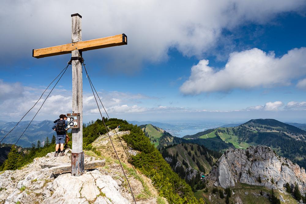 Gipfelkreuz auf dem Risserkogel vor dem Panorama von Tegernsee und dem Mangfallgebirge, Bayern, Deutschland