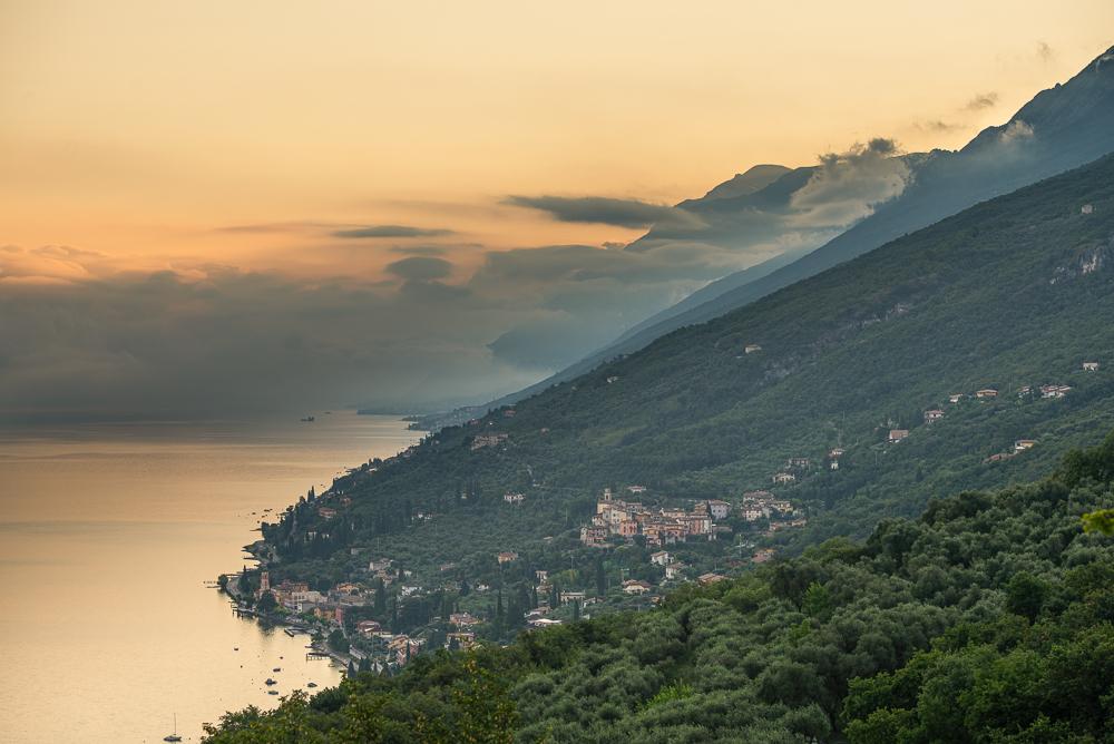Wolkenfetzen in der Morgensonne über dem Monte Baldo und dem nördlichen Gardasee, Veneto, Trentino, Italien