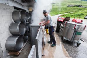 Mann reinigt die Behälter für die Rohmilch mit heißem, dampfenden Wasser vor der Käserei auf der Ackernalm, Tirol, Österreich