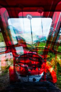 Blick über das Lenkrad aus der Fahrerkabine eines Linder-Traktors auf die Ackernalm, Tirol, Österreich