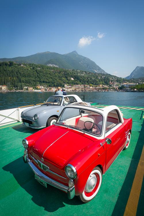 Ein roter Autobianchi Bianchina Trasformabile Oldtimer und grauer Nissan Figaro Cabrio auf dem Deck einer Fähre auf dem Gardasee, Italien