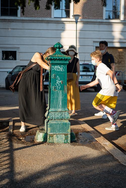 Touristen erfrischen sich an einem Brunnen am Castel San Pietro in der Altstadt von Verona, Venetien, Italien