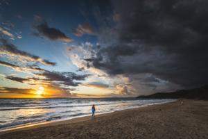 Frau spaziert auf Sandstrand vor dem Sonnenuntergang und dramatisch beleuchteten Wolken, Punta Ala, Toskana, Italien