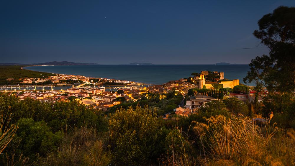 Blick über die Festung, die Stadt und den Hafen von Castiglione della Pescaia auf eine weit geschwungene Bucht der Küste der Maremma in der Dämmerung, Toskana, Italien