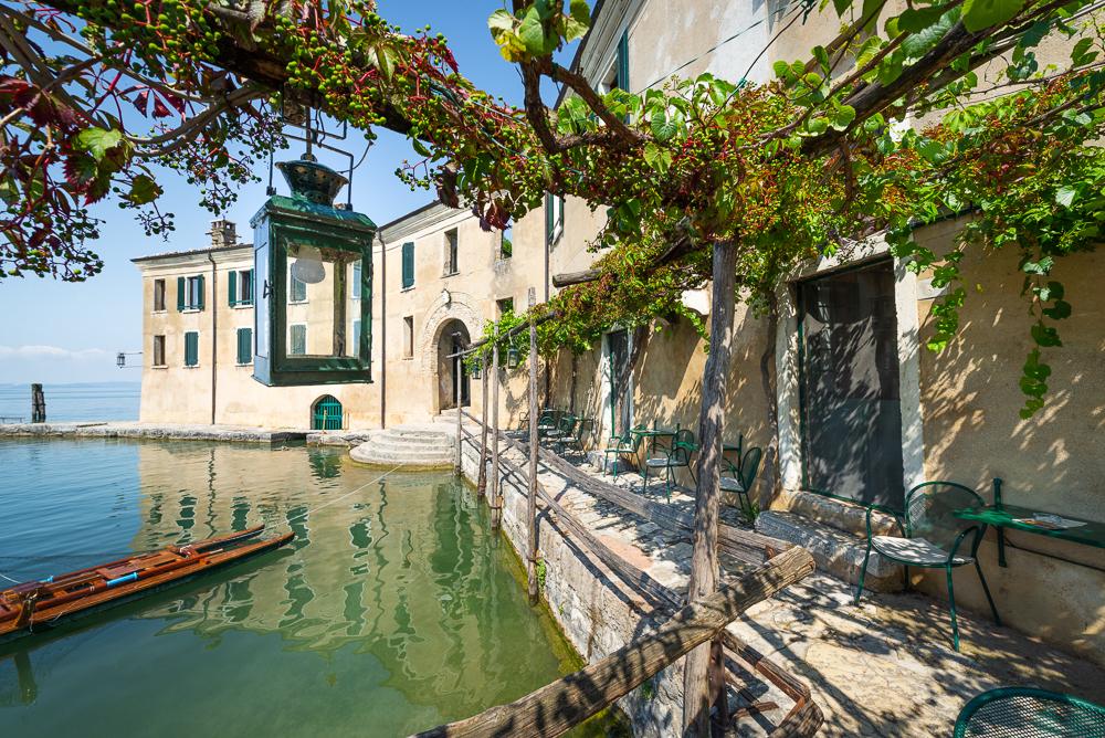 Laterne unter Weinreben im Cafe der Locanda San Vigilio am Gardasee in der Morgensonne, Venetien, Italien
