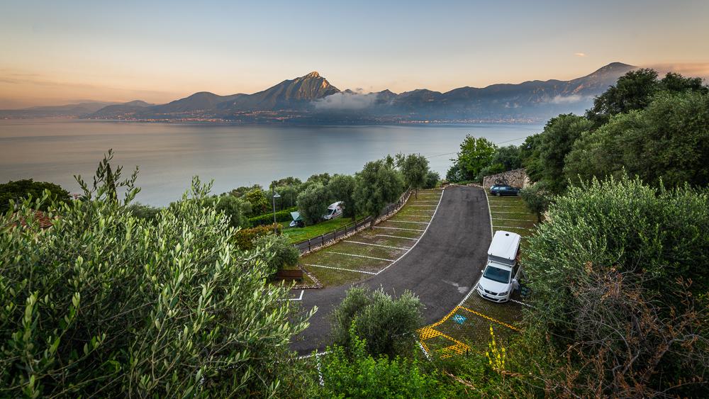 Unser Auto mit Dachzelt auf einem Parkplatz bei Crero mit Panorama vom Gardasee. Veneto, Italien