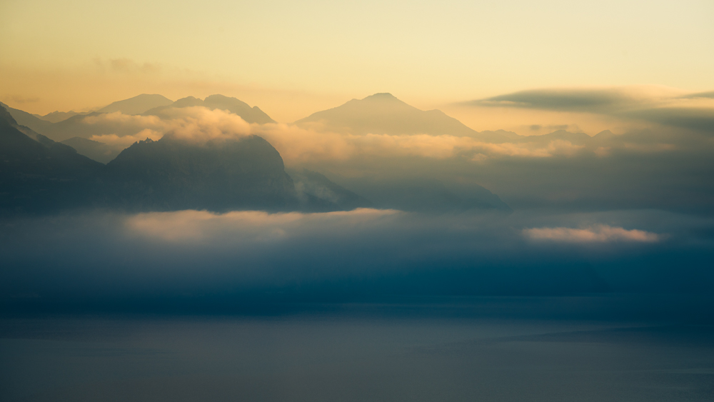 Wolkenfetzen und Nebelschwaden in der Morgensonne über dem nördlichen Gardasee, Veneto, Trentino, Italien