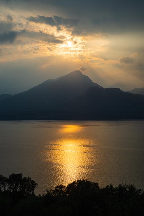Abendsonne scheint durch Gewitterwolken über dem Monte Pizzocolo und dem Gardasee, Italien