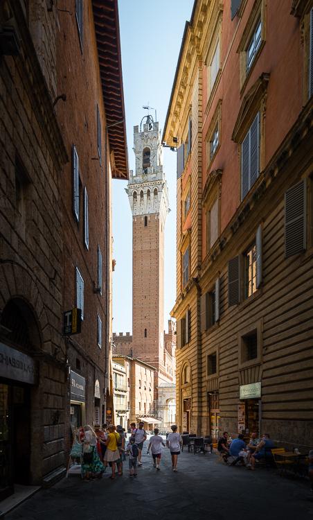 Blick aus einer schattigen Gasse in der Altstadt von Siena auf den in der Sonne leuchtenden Turm des Palazzo Pubblico an der Piazza del Campo, Toskana, Italien