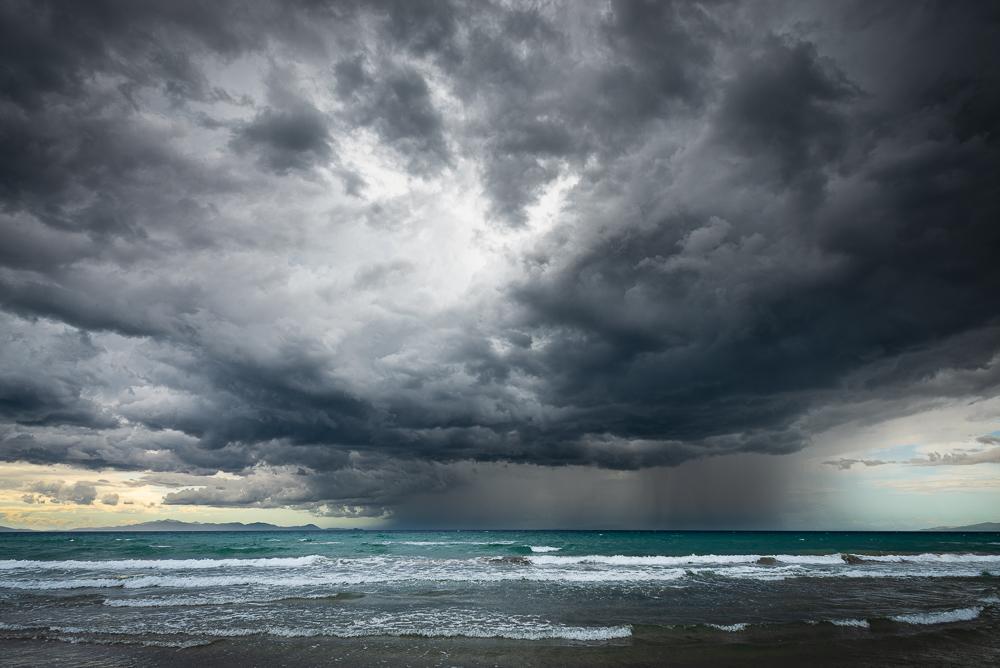 Gewitterzelle mit Regenschauer zieht über Elba und das Meer an die toskanische Küste bei Punta Ala, Toskana, Italien